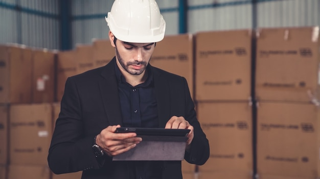 倉庫または工場でタブレットコンピューターを使用する工場長
