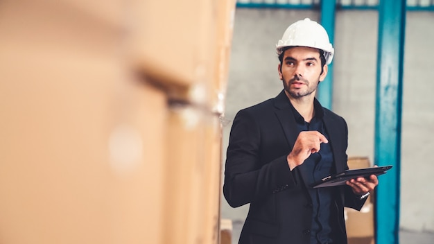 Factory manager using tablet computer in warehouse