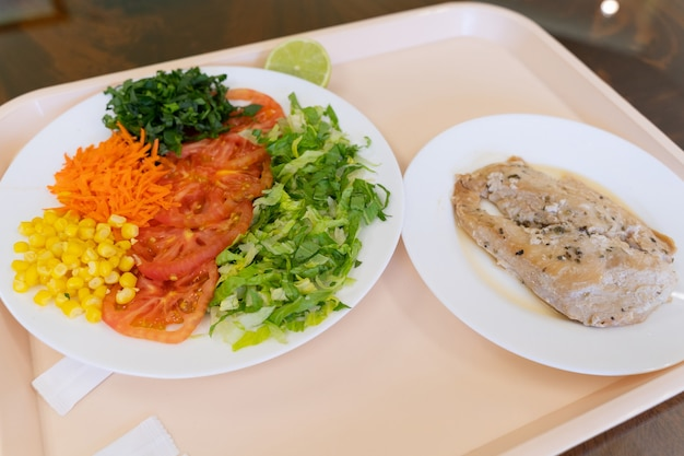 Factory menu tray with salad of lettuce tomato corn carrot and chicken steak lunch break concept