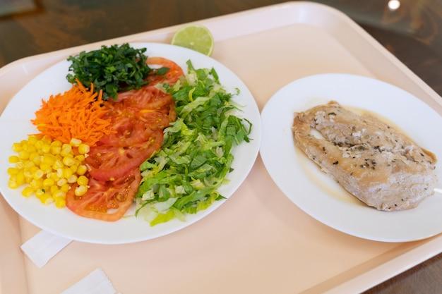 상추 토마토 옥수수 당근 샐러드와 치킨 스테이크 점심 시간 개념의 공장 메뉴 트레이