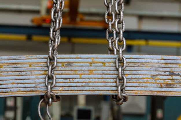 Factory overhead crane lifts iron strips on chains.
