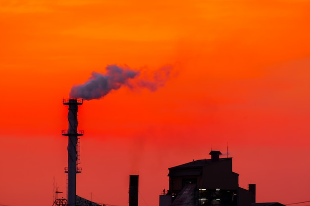 The factory released smoke chimney in sunset global warming
