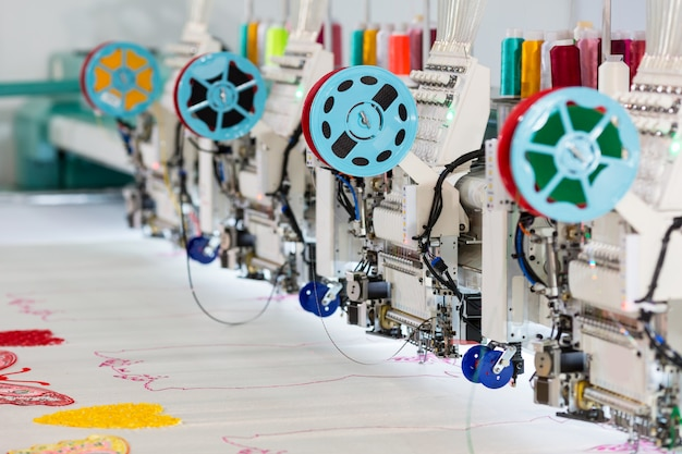 Factory sewing machine makes color pattern closeup. textile fabric, nobody. sew manufacturing, needlework technology
