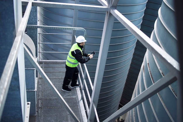 Factory silos worker standing on metal platform between industrial storage tanks and looking at tablet about food production