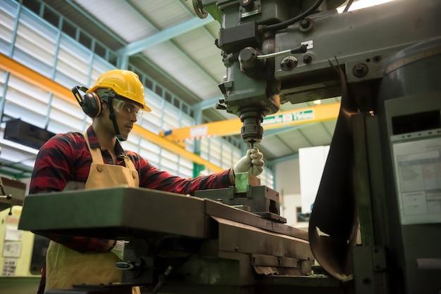 Рабочий заводского специалиста в шлеме и очках проверяет оборудование перед работой на фрезерном станке.