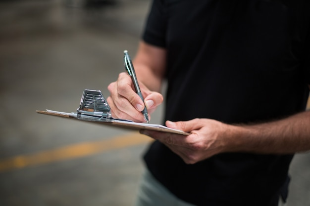 Factory staff writing on clipboard in factory