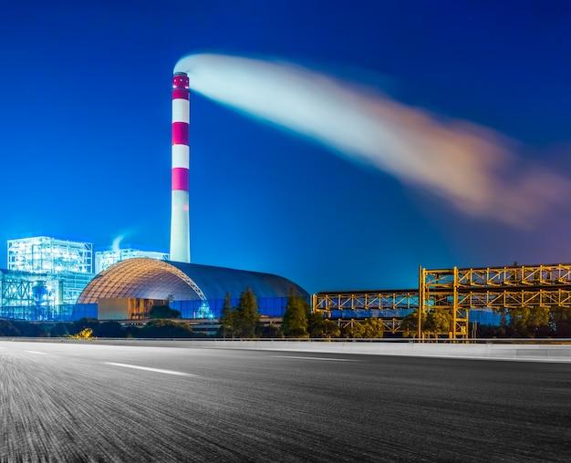 夜空に煙のスタックを持つ工場