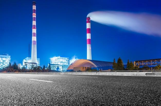 Фабрика с дымовой завесой против неба ночью