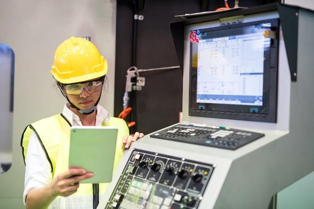 Factory worker check stock near machine monitor