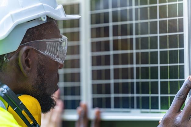作業服とヘルメットで持続可能な技術のために太陽電池パネルをチェックする工場労働者