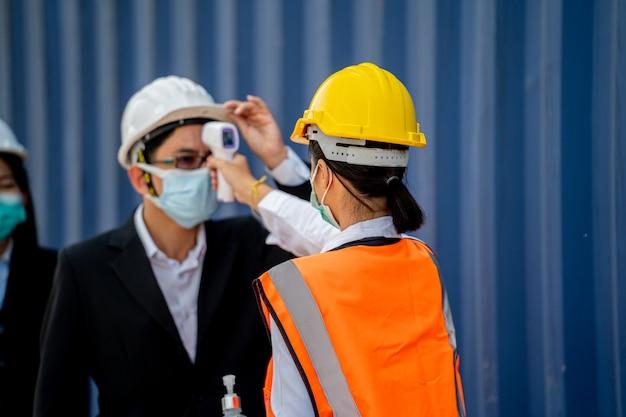 ビジネスマンの温度をチェックする工場労働者