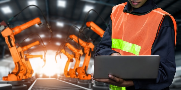 Заводской рабочий управляет роботизированной рукой на заводе