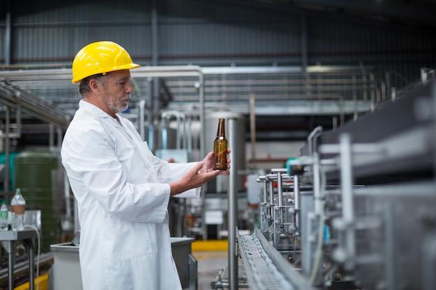 Фабричный рабочий осматривает бутылку на фабрике