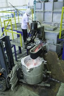 Рабочий завода по плавке металлического алюминия в ковше, стоящем на погрузочной машине