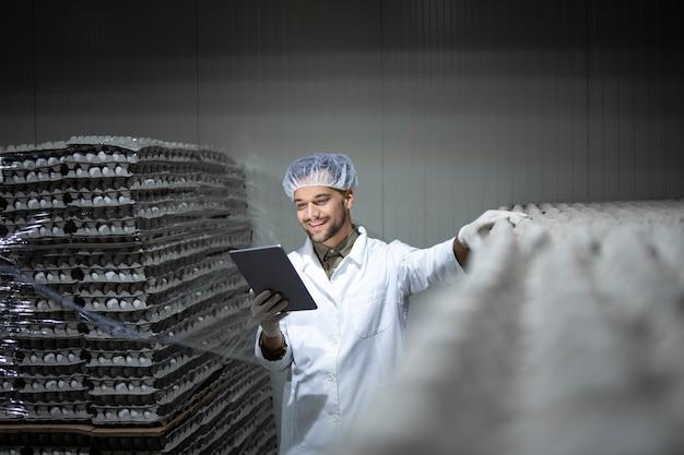 태블릿 컴퓨터를 들고 식품 냉장에 재고를 확인하는 공장 노동자.