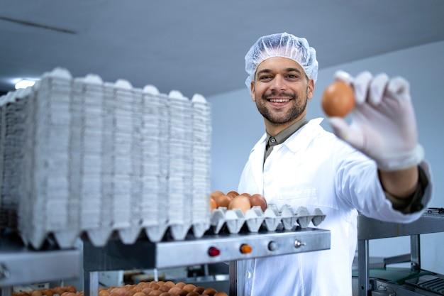 멸균 의류 헤어 넷 및 위생 장갑을 착용 한 공장 노동자가 계란을 들고 산업용 기계 분류 및 포장 작업