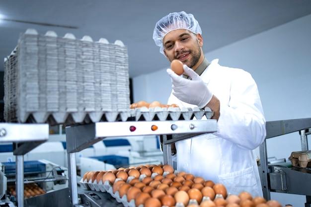 산업 기계를 포장하는 계란에서 일하는 멸균 의류, 헤어 네트 및 위생 장갑 공장 노동자. 유통 및 판매를위한 식품 준비.