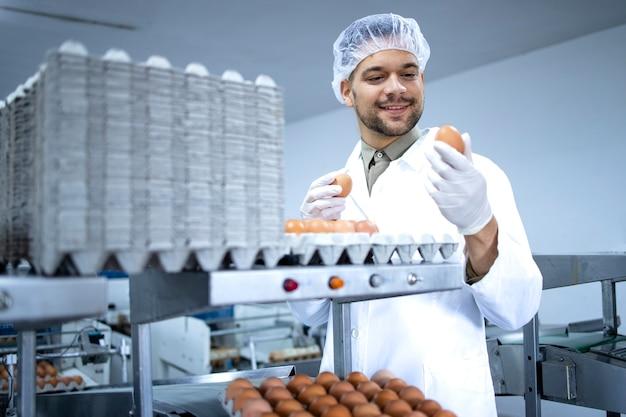 멸균 의류 헤어 넷 및 계란 포장 산업 기계에서 작업하는 위생 장갑 공장 노동자