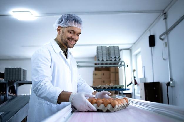 식품 가공 공장에서 산업용 계란 포장에 종사하는 멸균 의류, 헤어 넷 및 위생 장갑 공장 노동자.
