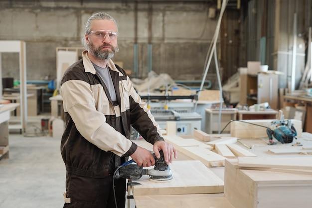 Заводской рабочий в униформе, стоящий у верстака с эскизами и деревянной заготовкой на встрече