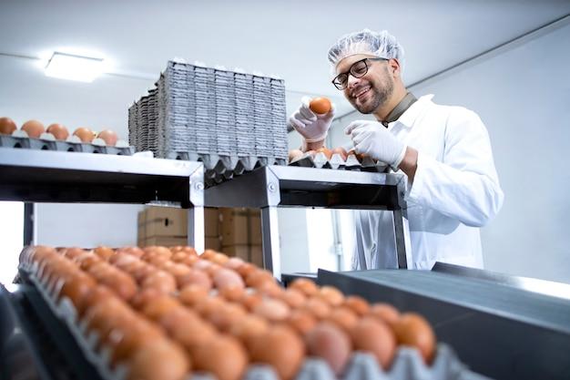 식품 가공 공장 또는 농장에서 산업적으로 생산 된 계란의 품질을 확인하는 흰색 코트와 헤어 넷의 공장 노동자.
