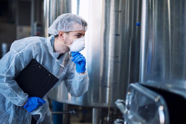 Заводской рабочий в белой защитной форме с сеткой для волос и маской смотрит на параметры промышленной машины
