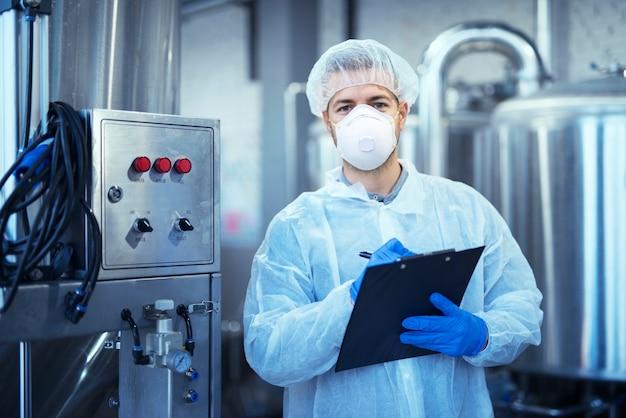 Заводской рабочий в белой защитной форме с сеткой для волос и маской стоит у промышленной машины
