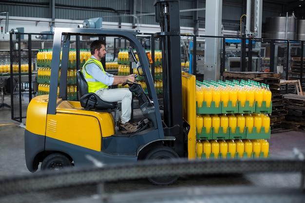 Factory worker loading packed juice bottles on forklift