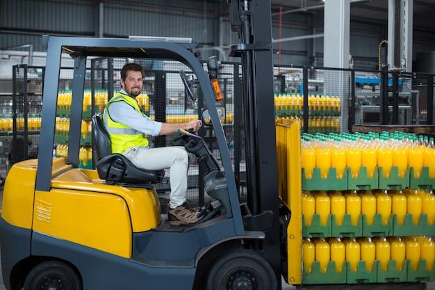工場のフォークリフトに詰められたジュースのボトルをロードする工場労働者