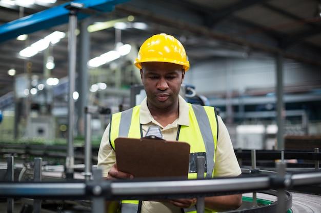 Фабричный рабочий, глядя на буфер обмена на заводе
