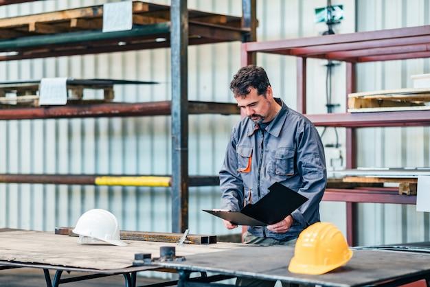 Фабричный рабочий, глядя на документы в промышленном зале.