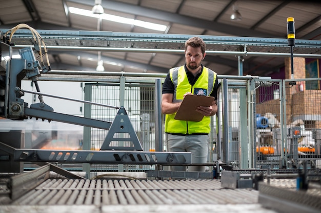 Factory worker maintaining record on clipboard in factory