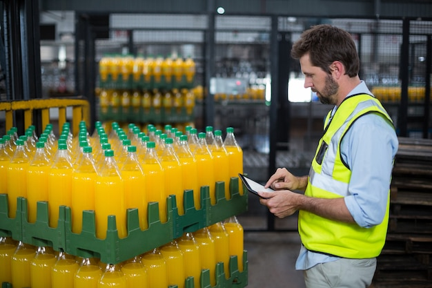 Factory worker maintaining record on juice bottles on digital tablet