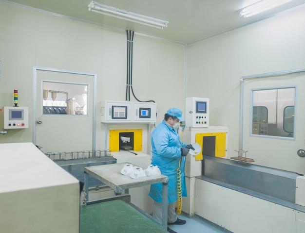 工場労働者は、車のヘッドライトの部品を手動で着色します。車のヘッドランプの部屋の色