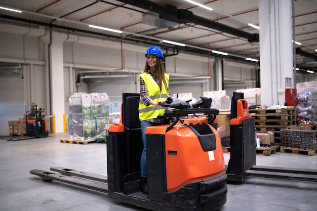 Factory worker in protective suit with hardhat driving forklift