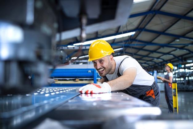 Operaio di fabbrica in uniforme protettiva e elmetto protettivo che opera macchina industriale alla linea di produzione