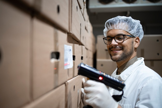 Factory worker scanning food packages with bar code scanner in cold storage.