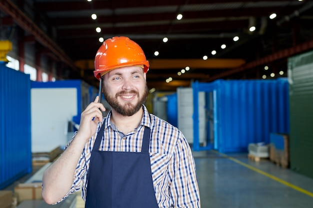 Factory worker speaking by phone