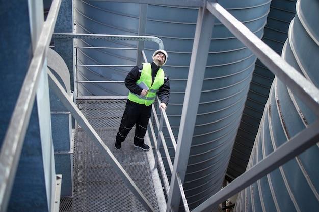 Operaio di fabbrica in piedi su una piattaforma metallica tra i serbatoi di stoccaggio industriali e guardando in alto per l'ispezione visiva della produzione alimentare di silos