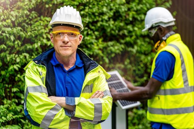 녹색 작업 스위트 드레스와 자신감을 가지고 서있는 공장 노동자 기술자 엔지니어 남자