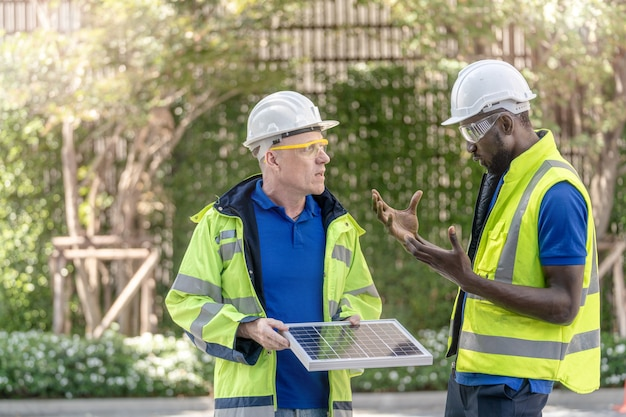 持続可能な技術のために太陽電池パネルをチェックする工場労働者の技術者エンジニアの男性
