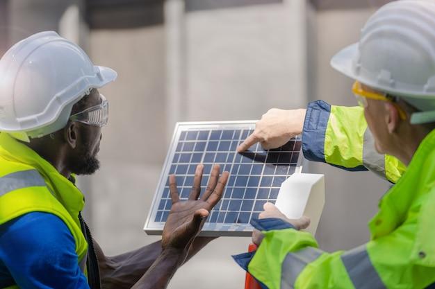 工場労働者の技術者エンジニアの男性が、作業用スーツとヘルメットを使用して太陽電池パネルの持続可能な技術を示し、チェックしています。