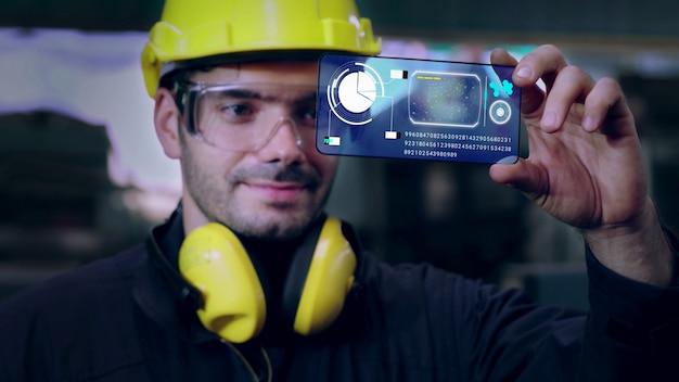 공장 작업자는 미래의 홀로그램 스크린 장치를 사용하여 제조를 제어합니다.