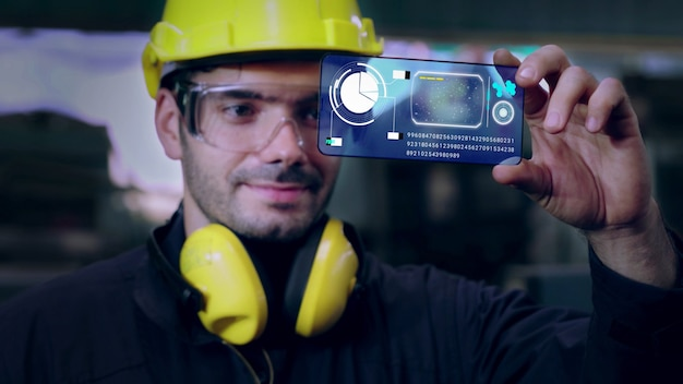 공장 노동자는 미래의 홀로그램 스크린 장치를 사용하여 제조를 제어합니다.