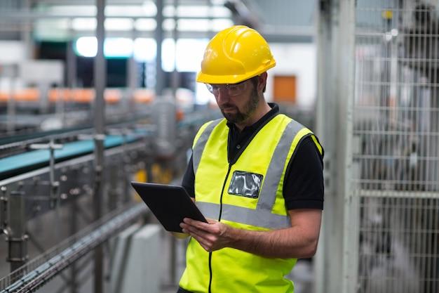 Фабричный рабочий с помощью цифрового планшета