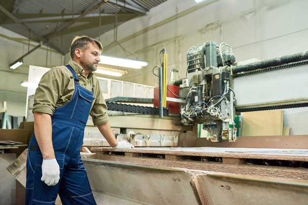 Фабричный рабочий, используя автомат для резки
