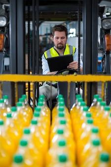 Factory worker using digital tablet in forklift