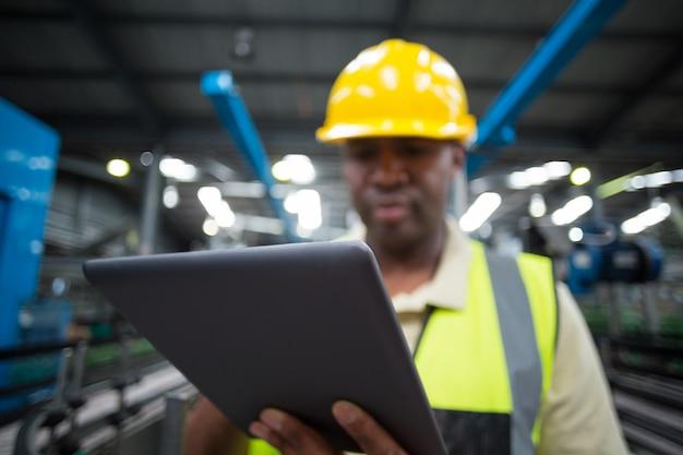 Фабричный рабочий с использованием цифрового планшета на заводе