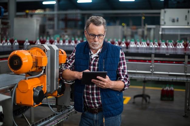 Фабричный рабочий с помощью цифрового планшета рядом с производственной линией