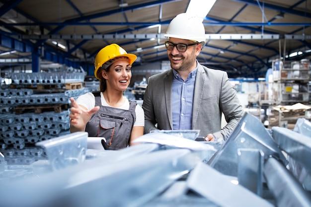 Заводской рабочий в каске и униформе показывает новые металлические изделия руководителю менеджера
